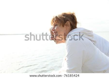 Senior couple in bathrobe standing on a pontoon - stock photo