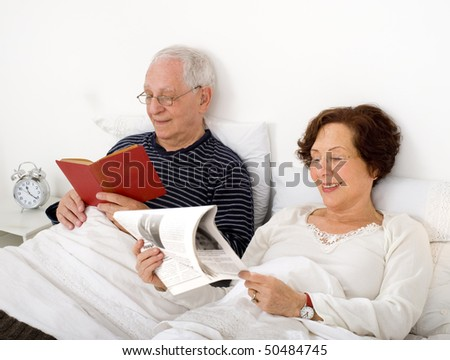 senior couple in bed with newspaper and book - stock photo