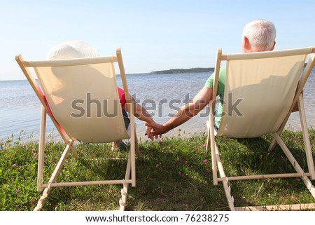 Senior couple in deck chairs in front of a lake - stock photo
