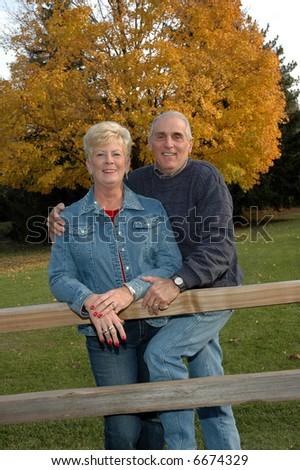 senior couple in front of an autumn tree - stock photo