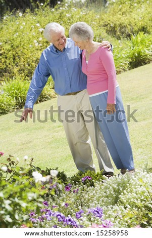 Senior couple in garden admiring flowerbed - stock photo