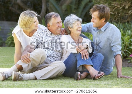 Senior Couple In Garden With Adult Children - stock photo