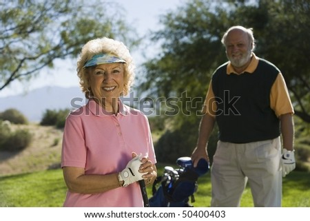 Senior couple in golf course, smiling, focus on woman, (portrait) - stock photo