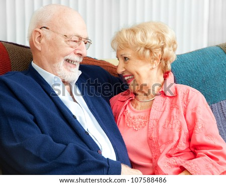 Senior couple in love, flirting on the couch. - stock photo