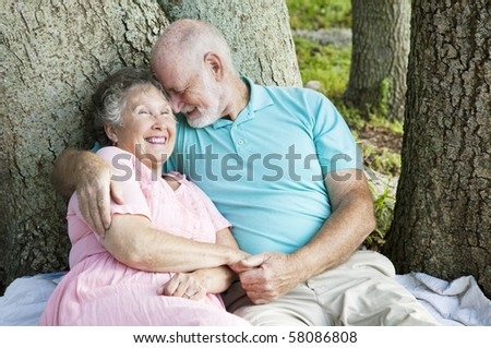 Senior couple in love.  He's whispering something funny in her ear. - stock photo