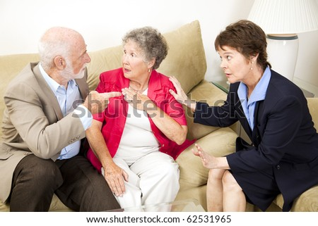 Senior couple in marriage counseling argues in front of their therapist. - stock photo