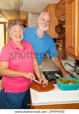 Senior couple in the kitchen of their motor home preparing lunch. - stock photo