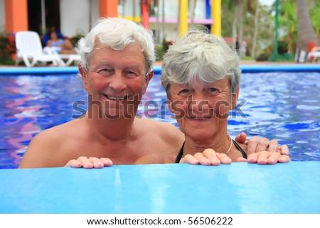 Senior couple in the swimming pool. - stock photo