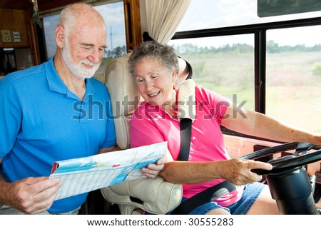 Senior couple in their motor home consulting a map. - stock photo
