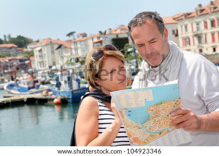 Senior couple in touristic area looking at map - stock photo