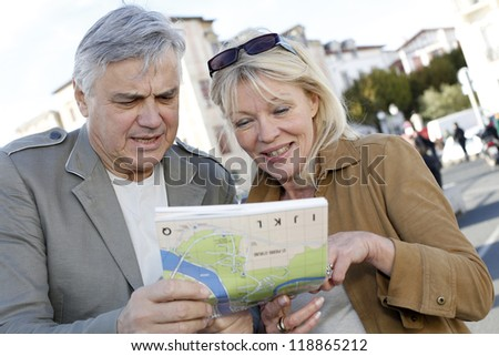 Senior couple in town looking at map and tablet