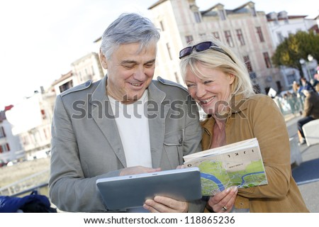 Senior couple in town looking at map and tablet - stock photo