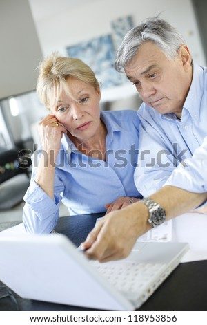 Senior couple inquiring bank website for help - stock photo