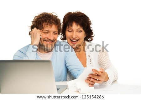 Senior couple laughing and holding receipt sitting by computer - stock photo