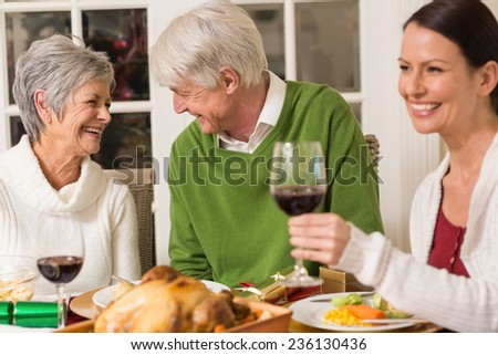 Senior couple laughing at christmas dinner at home in the lliving room