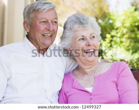 Senior couple laughing together sitting on garden seat - stock photo