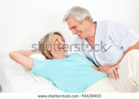 Senior couple laying laughing in bed in the bedroom