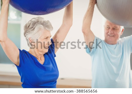 Senior couple lifting exercise ball while exercising