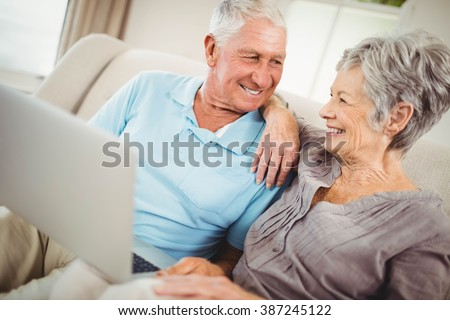 Senior couple looking at each other and smiling in living room - stock photo