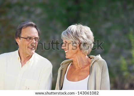 Senior couple looking at each other while smiling in park - stock photo