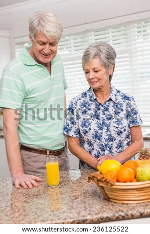 Senior couple looking at glass of orange juice at home in the kitchen