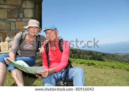 Senior couple looking at map on hiking day - stock photo
