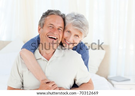 Senior couple looking at the camera  at home - stock photo
