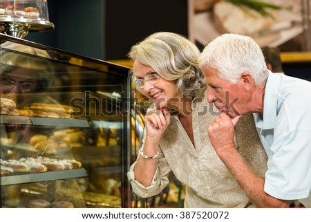 Senior couple looking puddings at the bakery store - stock photo