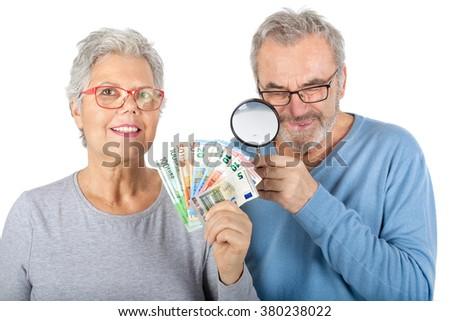 Senior couple looks through a magnifying glass on euro money - stock photo