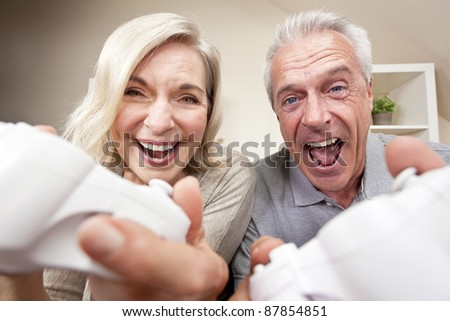 Senior couple, man and woman, laughing & having fun playing video console games together. - stock photo