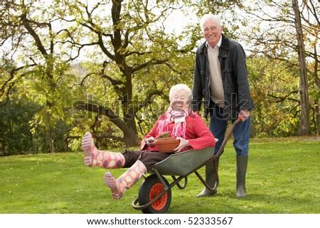 Senior Couple Man Giving Woman Ride In Wheelbarrow - stock photo