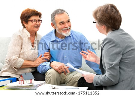 Senior couple meeting with real estate agent - stock photo