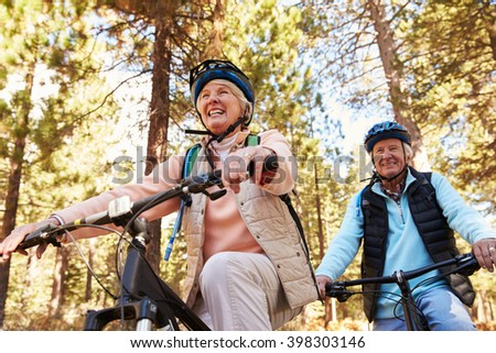 Senior couple mountain biking on a forest trail, low angle - stock photo