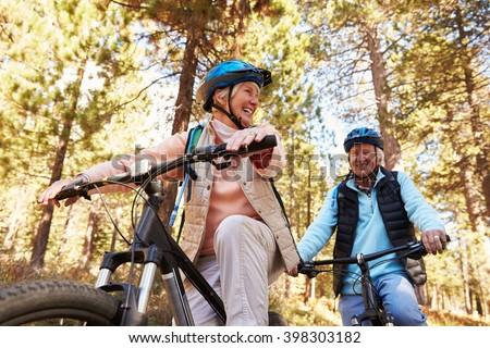 Senior couple mountain biking on a forest trail, low angle - stock photo