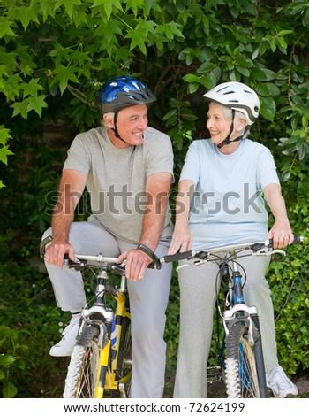 Senior couple mountain biking outside - stock photo