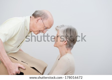 Senior couple moving to a new home sharing a moment of tenderness as they smile at each other over a brown cardboard carton - stock photo