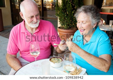 Senior couple on a date enjoys an artichoke dip appetizer. - stock photo
