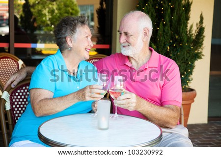 Senior couple on a romantic date, having cocktails at a restauraunt. - stock photo