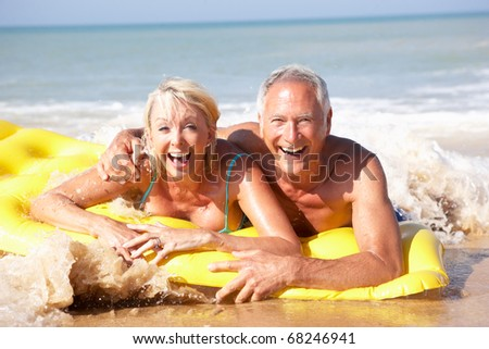 Senior couple on beach holiday - stock photo