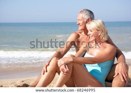 Senior couple on beach holiday - stock photo