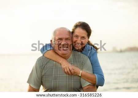 Senior couple on  beach in  sunset rays of  sun.
