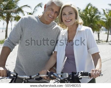 Senior couple on bicycles on tropical beach - stock photo