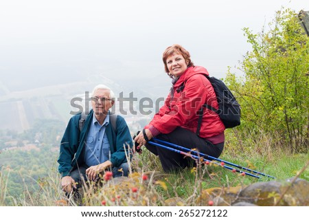 Senior couple on hiking trip resting in the nature. - stock photo