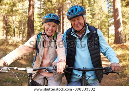 Senior couple on mountain bikes in a forest, portrait - stock photo