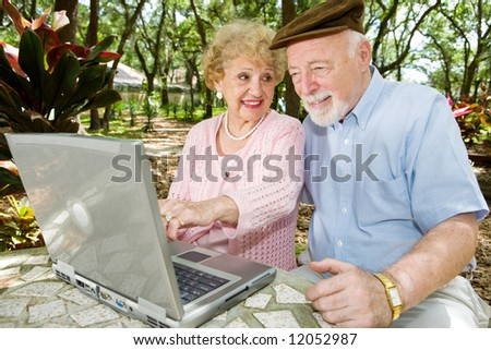 Senior couple on the computer.  The wife is pointing something out to the husband. - stock photo