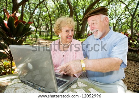Senior couple on their laptop computer in a beautiful, natural setting. - stock photo
