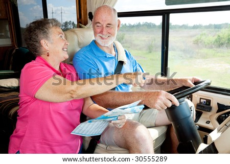Senior couple on vacation in their motor home.  The wife is reading the map for the husband. - stock photo