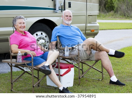 Senior couple on vacation, relaxing outside their motor home. - stock photo