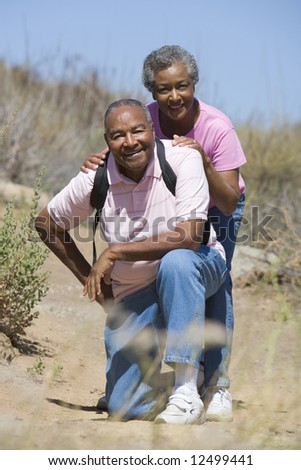 Senior couple on walk in countryside - stock photo