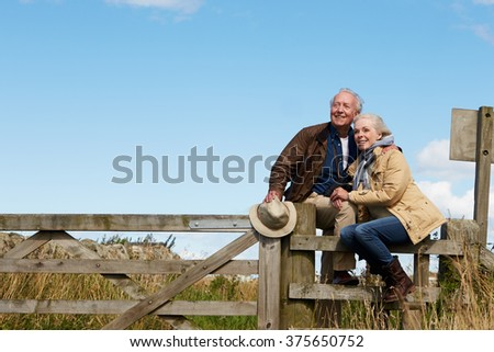 Senior Couple On Walk Leaning Against Wooden Gate - stock photo